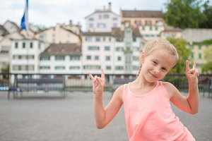 Adorable little girl outdoors in Zurich, Switzerland. Back view of kid background of beautiful city