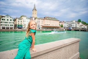 Adorable little girl outdoors in Zurich, Switzerland. Closeup portrait of kid background of beautiful city