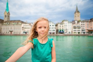 Adorable little girl taking selfie outdoors in Zurich, Switzerland. Closeup portrait of kid background of beautiful city