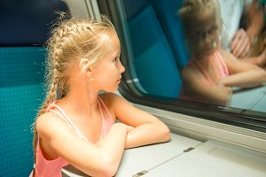 Adorable little kid looking out train window outside, while it moving.