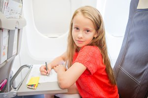 Adorable little girl traveling by an airplane. Kid drawing picture with colorful pencils sitting near window