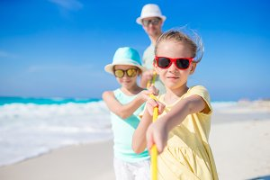 Family of dad and kids have fun on white tropical beach