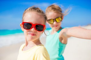 Cute little girls taking selfie at tropical beach on exotic island during summer vacation