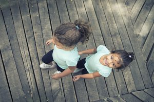 Two happy little kids on wooden floor
