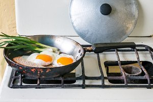 fried eggs, green onion and bread in old frying pan