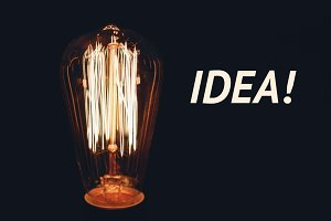 Inscription Idea on the image of retro bulb on a black background.