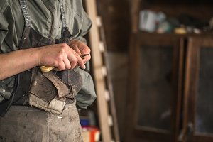 male carpenter working with a wood product, hand tools