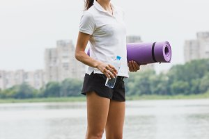 Sporty attractive woman on the lakes coast with a mat and bottle with water