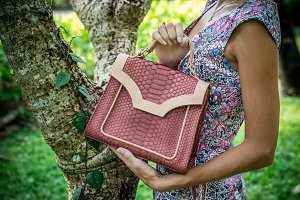 Young woman holding a luxury handmade snakeskin python handbag. Sunny day. Expensive clutch. Close up of woman hands with bag.