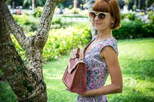 Outdoor fashion portrait of glamour sensual young stylish lady in sunglasses with luxury handmade snakeskin python bag. Python handbag. Sunny day, green plants, tropical palms. Bali island.