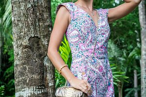 Outdoor fashion portrait of glamour sensual young stylish lady in sunglasses with luxury handmade snakeskin python bag. Python handbag. Sunny day, green plants, tropical palms. Bali island.