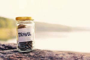 coin on glass jar with travel word