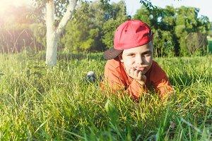 Little boy lies on the green grass in the garden