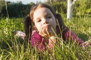 Little girl lies on the green grass in the garden