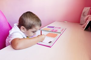 Little boy drawing on notebook