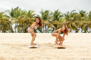 Beautiful girls with surf on beach.
