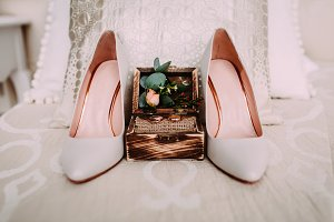 Wooden box with gold wedding rings and flowers stand next to elegant bridal shoes