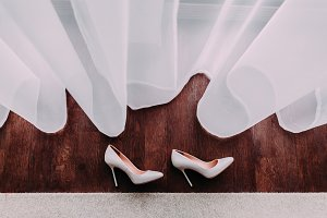 Elegant bridal shoes lying on the wooden floor next to the window.