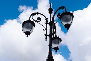 Vintage lamp on blue sky with clouds background