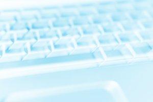 Diagonal cyan laptop keyboard bokeh background