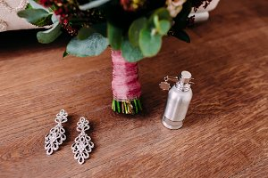Elegant bridal earrings and perfume on the wooden floor next to the wedding bouquet
