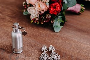 Beautiful bridal earrings and perfume on the wooden floor next to the wedding bouquet