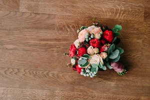 Wedding bouquet of red and cream roses on a wooden floor. Top view