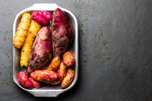 Peruvian raw ingredients for cooking - yuca, colored sweet potatoes and camote batata. Top view