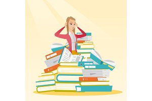 Student sitting in huge pile of books.