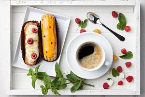 Coffee drink with eclairs in wooden tray