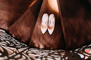Peach bridal wedding shoes on wooden stairs with decorative railings