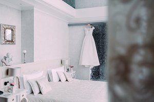 White elegant bridal dress hanging on a wooden hanger in luxury hotel room in minimalist style
