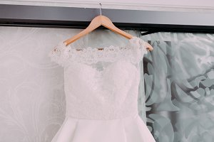White beautiful bridal dress with lace on a wooden shoulders, before wedding ceremony