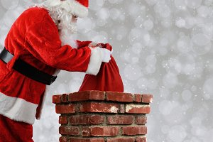 Santa Claus Putting Bag into Chimney