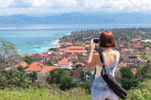 Young woman tourist making photos of panorama tropical island Nusa Lembongan, Indonesia. Holding her smartphone. Clear sunny day. View from the cliff.