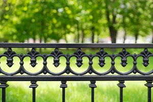 Horizontal park fence with green bokeh background