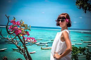 Portrait of a beautiful healthy young woman near the ocean with blue water and flowers. Tropical island Bali, Indonesia, Asia.