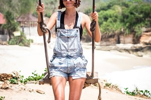 Vacation concept. Young woman swing on a beach swing on the cliff. Selective focus. Tropical island Nusa Lembongan, Indonesia. The ocean on a background.