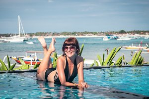 Portrait of beautiful tanned woman in black swimwear relaxing in swimming pool spa. Hot summer day and bright sunny light. Beautiful ocean, sky and asian plants on the background. Tropical island Bali, Indonesia.