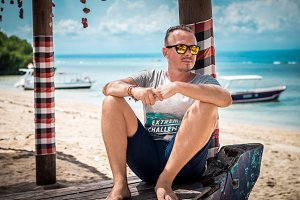 Portrait of an attractive young caucasian man with sunglasses posing on a tropical beach of Nusa Lembongan, Indonesia. Sunny day summer.