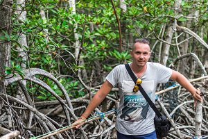 Portrait of a handsome caucasian man in the jungle near the river in mangrove forest. Tropical island Nusa Lembongan, Indonesia, Asia.