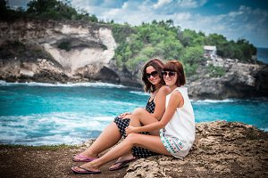 Two happy young female friends sitting on the cliff, ocean on a background. Happy vacation in Asia, Indonesia. Two smiling youn women.
