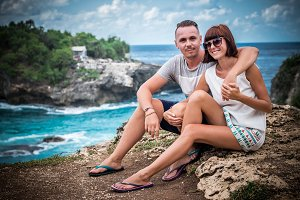 Attractive young happy romantic couple on the tropical island Nusa Lembongan, Indonesia. Happy honeymoon during their vacation in Asia. Romantic scene on the cliff. Ocean on a background.