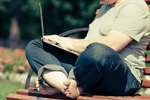 Man sitting on a Bench with laptop
