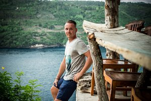 Portrait of a handsome caucasian man on the tropical island Bali, Indonesia. Sunny day, cliff, asian trees and river on a background.