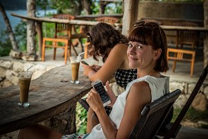 Best friends having fun, laughing. Tropical cafe on the cliff in Nusa Lembongan, Indonesia. Girls drinking ice coffee.
