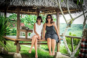Two Beautiful happy young girls sitting in a wooden gazebo at sunny day. and having fun, smiling and laughing. Tropical Bali island, Indonesia.