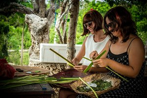 Two young caucasian pretty woman preparing balinese hindu offerings to Gods in wooden gazebo. Tropical island Bali, Indonesia.