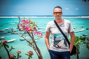 Portrait of a handsome caucasian man on the tropical island Bali, Indonesia. Sunny day, ocean, flowers and boats on a background.