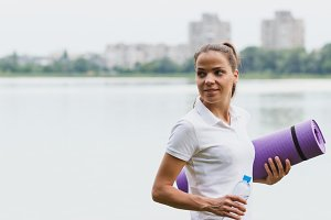 Sporty attractive woman on the lakes coast with a mat and bottle with water,